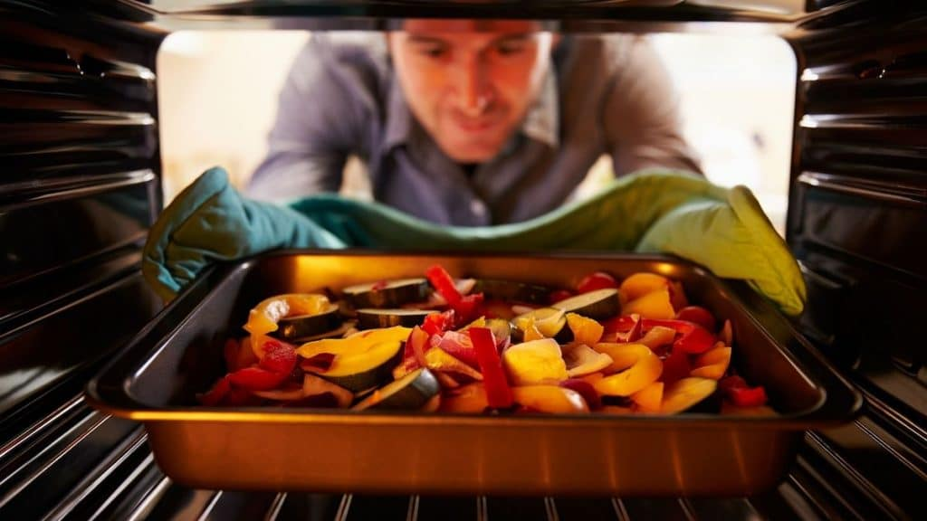 A picture showing fresh vegetables going in the oven