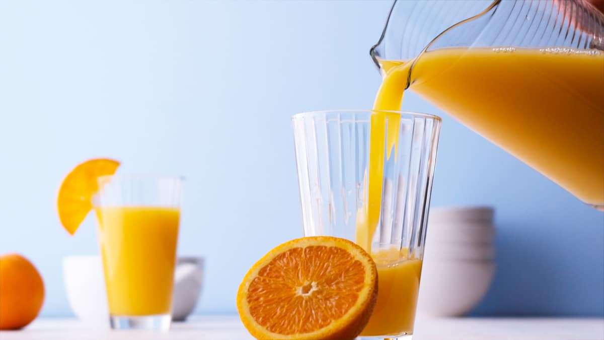 A picture of fresh orange juice being poured into a glass