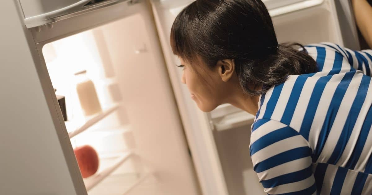 Woman putting her chocolate easter egg in her fridge