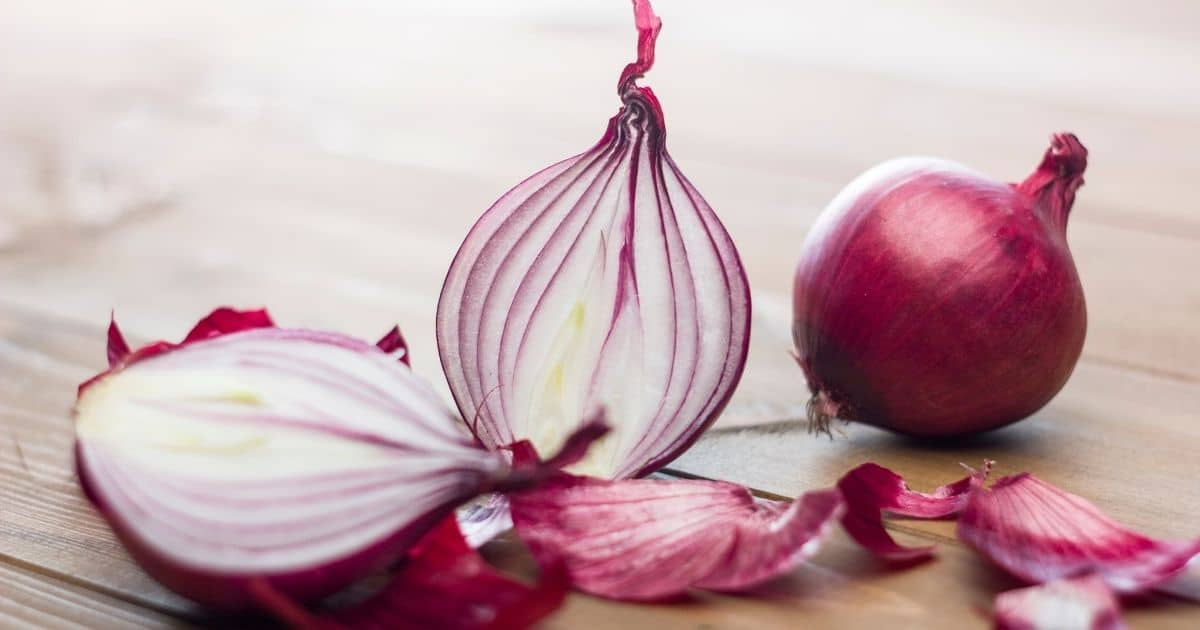 Red onions cut half on a wooden desk.