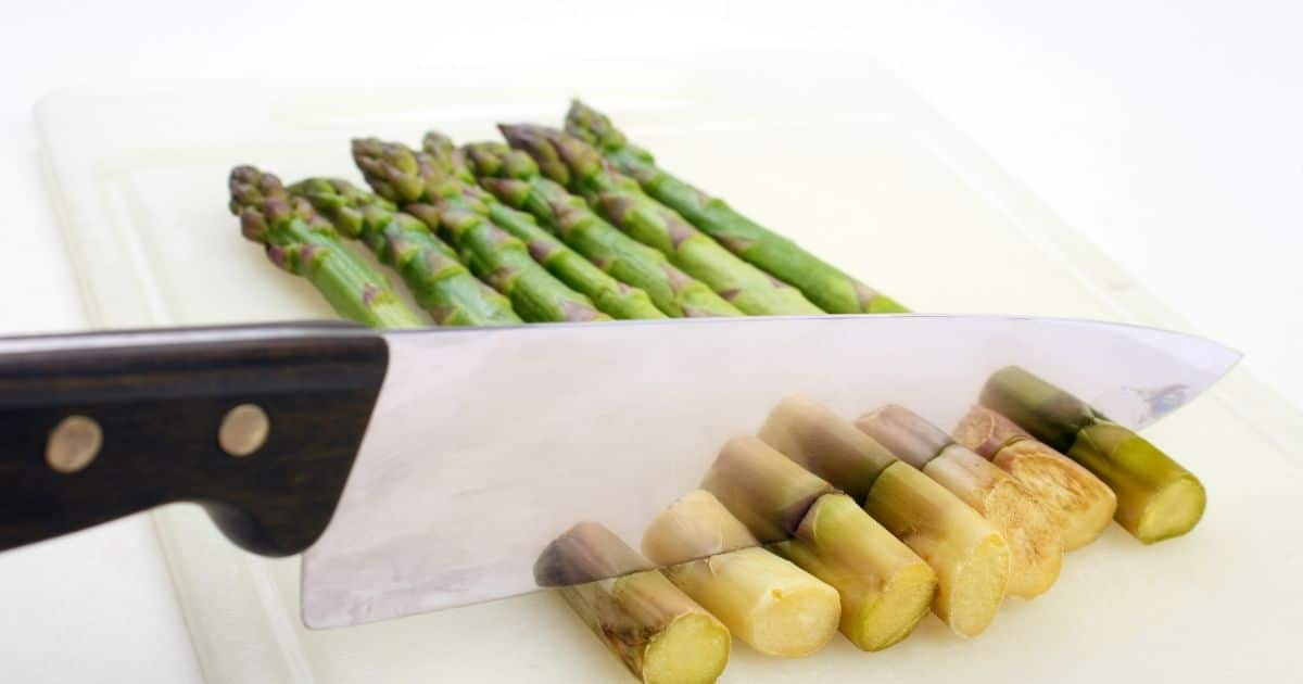 The bottom of the asparagus being cut
