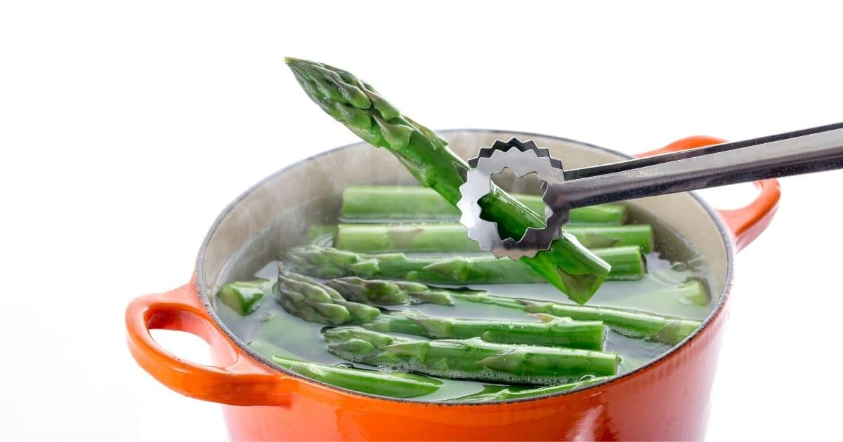 Asparagus being added into boiling water with tongs