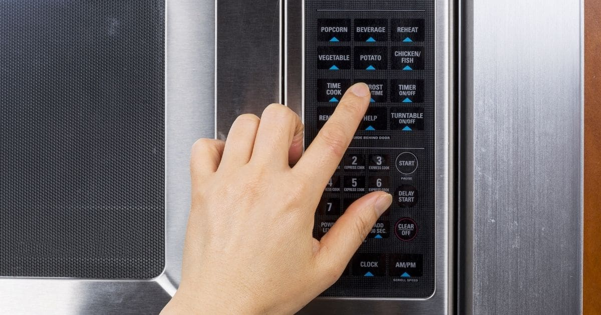 A hand using the defrost function in a microwave